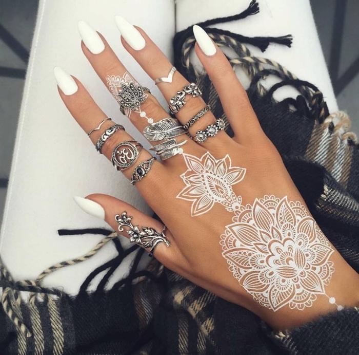 tatouage temporaire, dessin au henné blanc sur la main, bijoux métalliques à design feuilles et fleurs