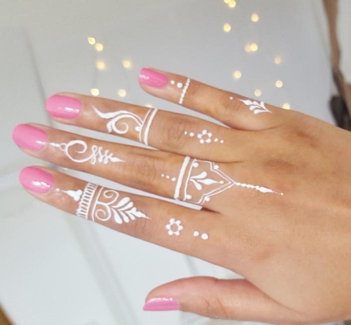 modele henné, tatouage blanc sur les doigts à design gouttes d'eau et volutes, manucure ongles rose