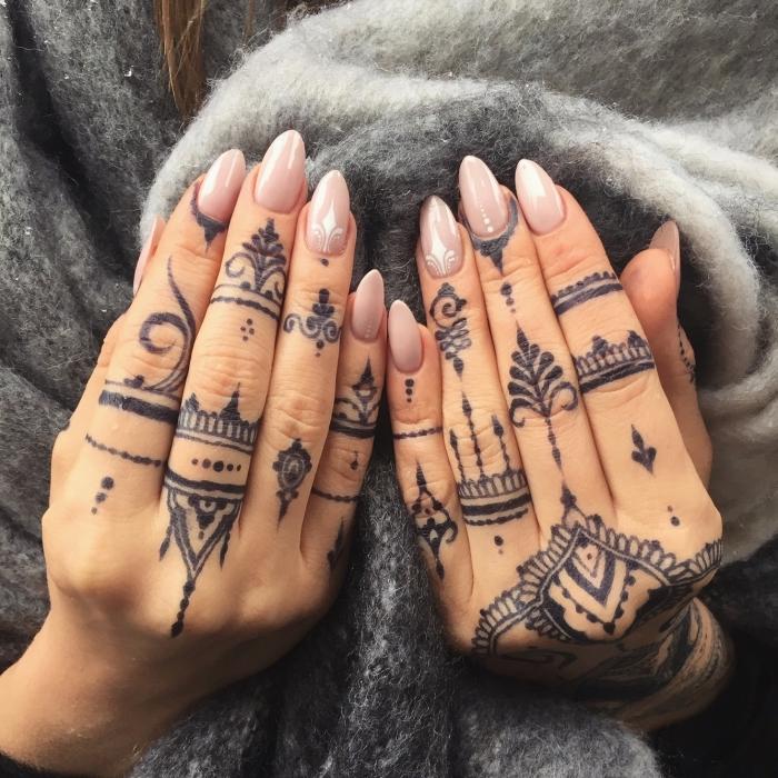 modele henné, ongles longs au vernis rose avec décoration blanche à design ethnique, tatouage temporaire pour femme
