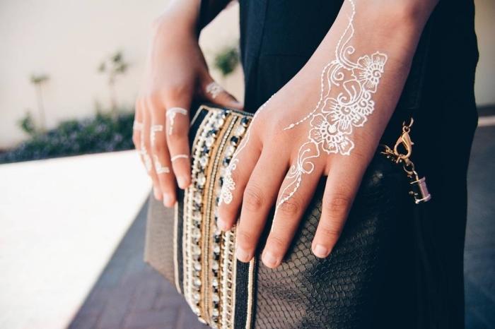 modele henné, tatouage temporaire au henné blanc à design florale sur les doigts, modèle de pochette noire avec décoration en dentelle