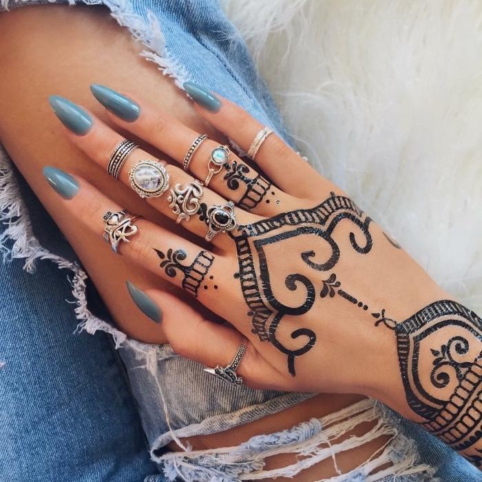 modele henné main, manucure aux ongles longs et vernis bleu foncé, bijoux métalliques et tatouage ethnique