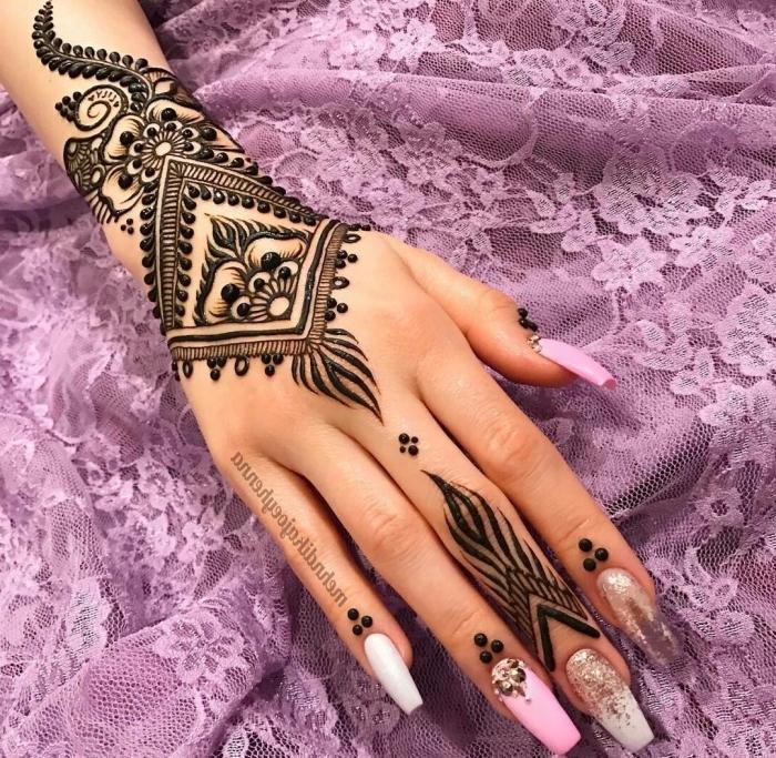 modele henné main, dessin sur la main et les doigts au henné noir, tatouage temporaire à design ethnique