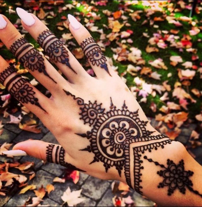 henné tatouage, dessin sur les mains et les doigts pour femme, manucure ongles longs à vernis rose pâle