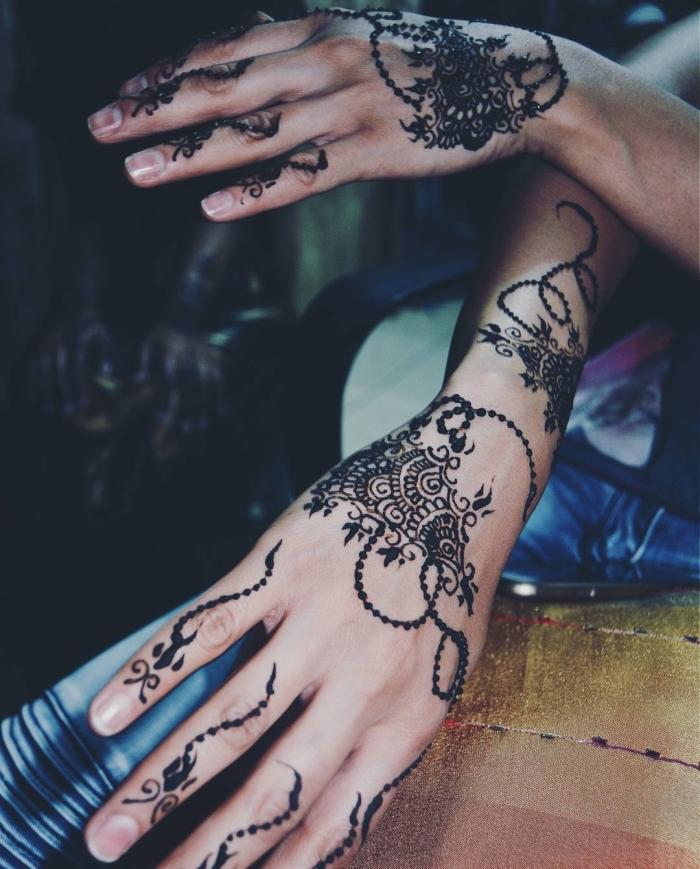 tatouage temporaire, dessin sur les mains et les doigts au henné noir, tattoo à motifs gouttes d'eau et fleurs