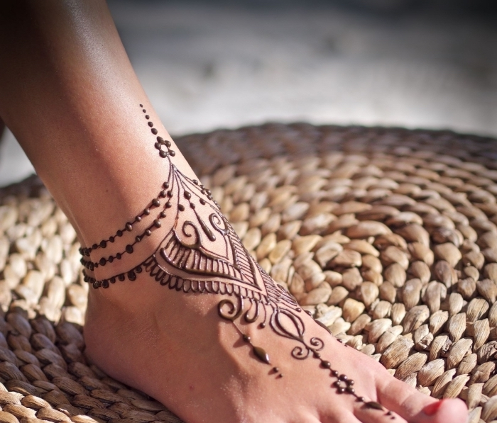 tatouage henne, décoration sur la peau au henné noir, tattoo temporaire pour femme à design bracelet cheville
