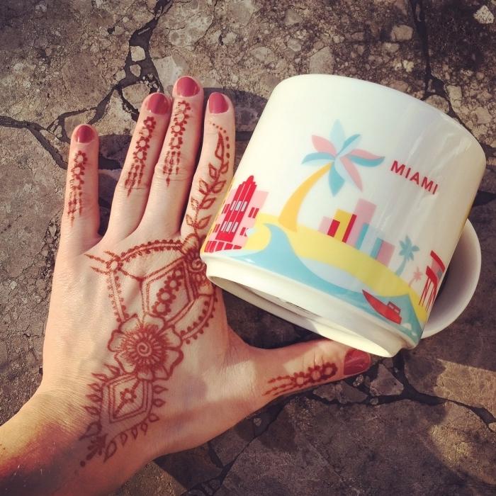 tatouage au henné rouge à design florale sur les doigts et les mains, art corporel temporaire pour femme