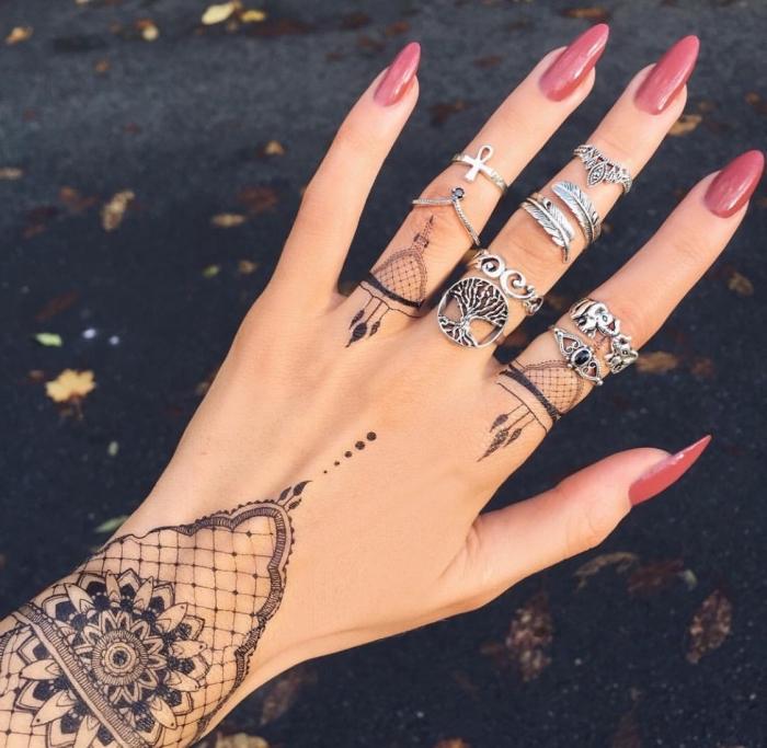 dessin henné, manucure aux ongles longs et vernis rouge, henné noir à design dentelle et bracelet sur la main féminine