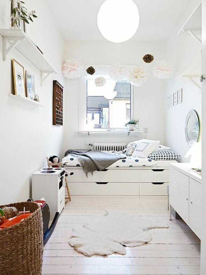 décoration chambre adulte en blanc avec tapis en forme irrégulière, luminaire en forme de grande boule en carton, étagères blanches, pompons décoratifs en carton coloré en rose poudré