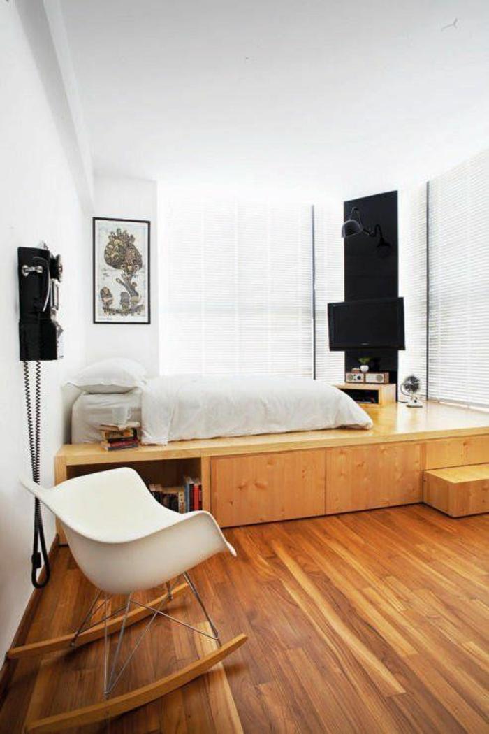 décoration chambre adulte avec lit sur plate-forme et chaise balançoire en plastique blanche, , partie de mur peinte en noir, pour délimiter l'espace télévision, revêtement du sol en couleur whisky, parquet massif