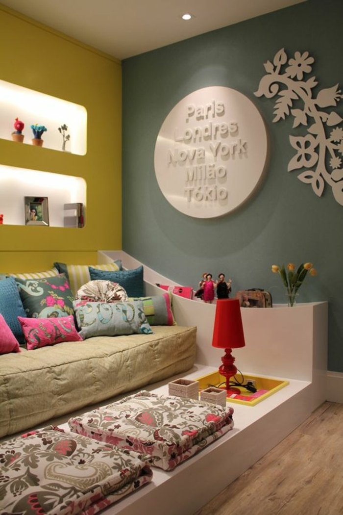 décoration chambre adulte en bleu pétrole et jaune moutarde, lit monté sur plate-forme, avec des coussins colorés aux motifs fleuris, sol recouvert de revêtement imitation bois en couleur marron clair