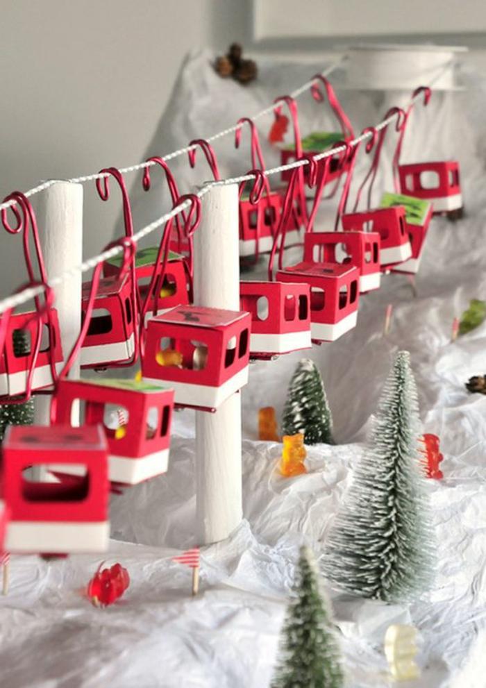 idées déco de Noel, téléférique et sapins, cabines rouges avec petits bonbons