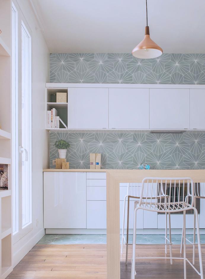 papier peint céladon couleur, façade cuisine blanche avec plan de travail et bar en bois, parquet clair, suspension cuivre, chaises metalliques blanches