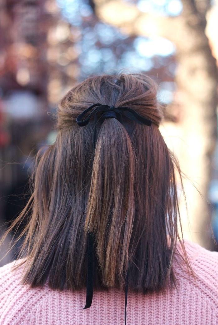 une coiffure simple cheveux mi long à demi queue-de-cheval attachée avec ruban noir