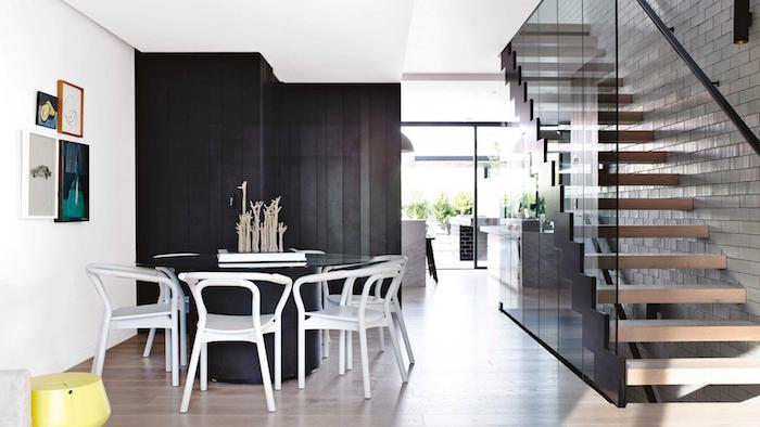 comment aménager une cuisine en longueur cuisine grise avec bar en marbre ouverture sur une salle à manger avec table ronde noire et chaises blanches, escalier en bois