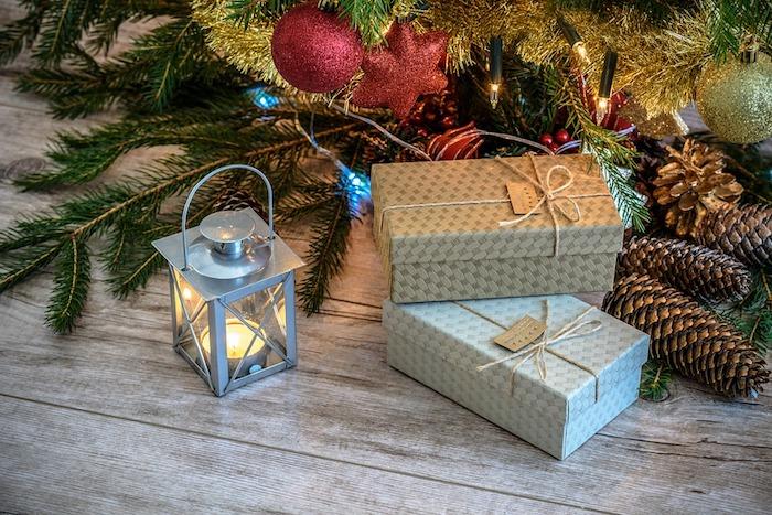 comment décorer un sapin de noel, que mettre au peid du sapin, déco en lanterne grise, paquet cadeau gris, pommes de pin