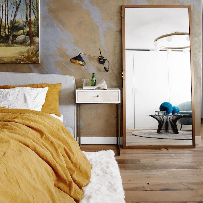 idée pour décorer sa chambre, parquet bois clair, linge de lit blanc et jaune moutarde et tapis moelleux, mur jaune avec eclats violets, grand miroir avec cadre bois