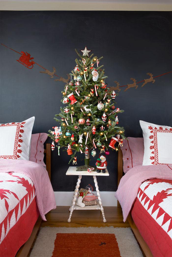 exemple de décoration sapin de noel en ornements rouges et blancs, motif père noel, petites figurines festive, deux lits avec linge de lit rouge et blanc
