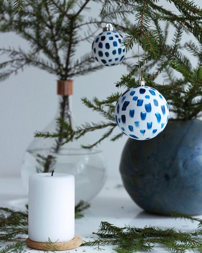 comment fabriquer une boule de noel blanche avec decoration de touches de peinture bleue, brins de pin dans un vase en verre, bougie blanche