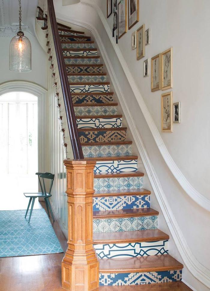 papier peint à motifs blancs, beiges et bleus sur les contremarches, marches et rambarde en bois, mur de cadres sur la montée d escalier, suspension originale