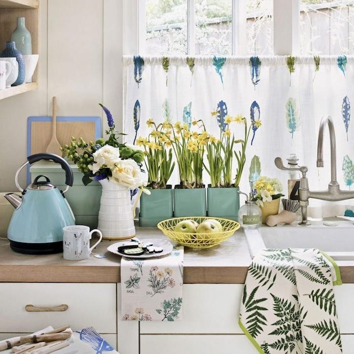 des accessoires deco bleu celadon, meuble cuisine blanc avec plan de travail en bois et étagères en bois, plusieurs plantes vertes, rideau à plumes bleues, vertes et violettes