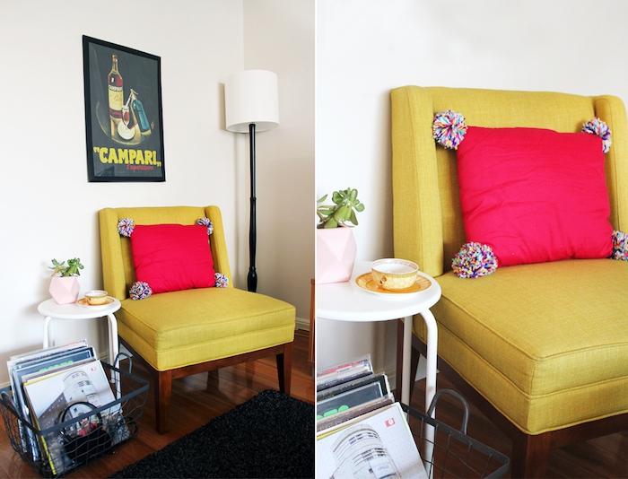 diy déco chambre avec un coussin rouge décoré de pompons colorés sur un fauteuil jaune, parquet marron, tapis noir, affiche decoratif