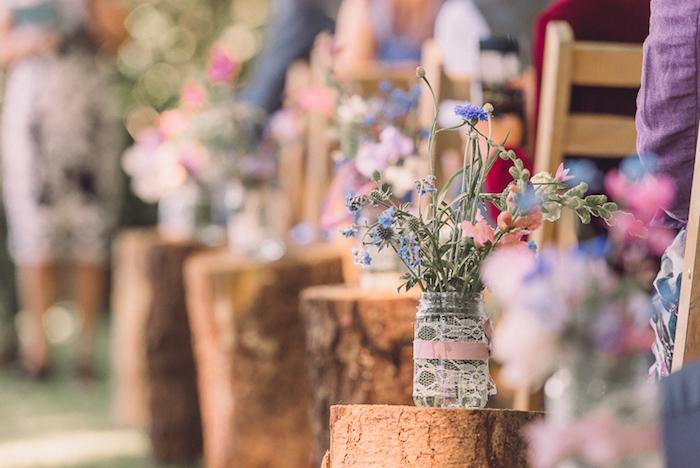 deco champetre cérémonie mariage en bûches en bois décorés de pots en verre, décorés de dentelle et ruban rose et fleurs champetre