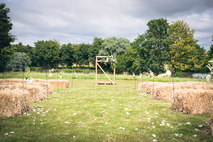 décor mariage champetre chic sur une pelouse, des meules de foin en guise d assises, arche en bois fleurie