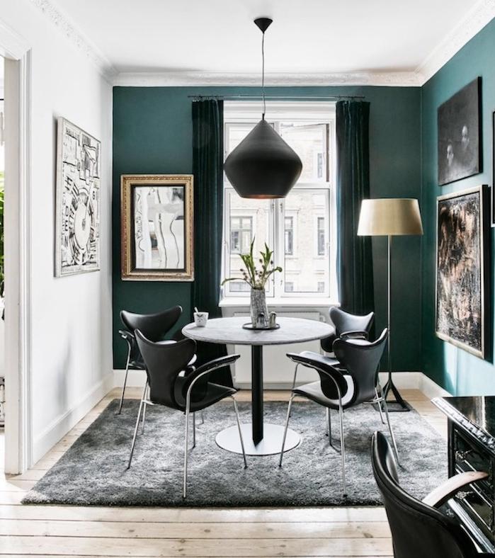 idée de deco bleu canard, nuance pétrole sur un seul pan de mur, parquet bois clair, table grise, entourée de chaises noires, tapis gris anthracite, suspension noire, decoration murale de cadres peinture abstraite