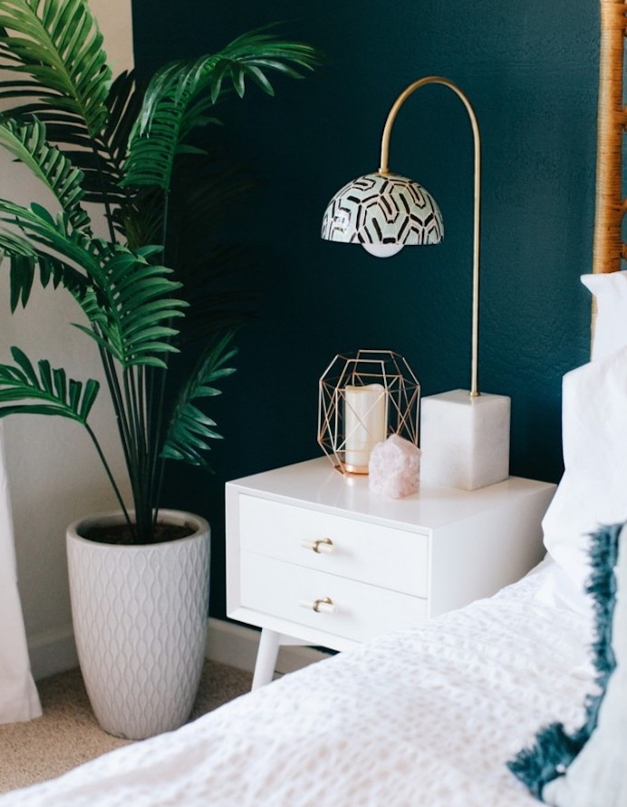 idée de déco chambre à coucher design scandinave avec un mur de fond peinture bleu paon, table de nuit avec tiroirs blanche, linge de lit blanc, tapis gris, lampe bougie, palmier vert