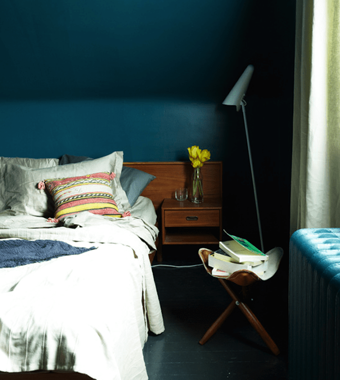 bleu petrole peinture pour une chambre sous pente, linge de lit gris, table de nuit en bois, parquet gris anthracite, tabouret rangement de livres
