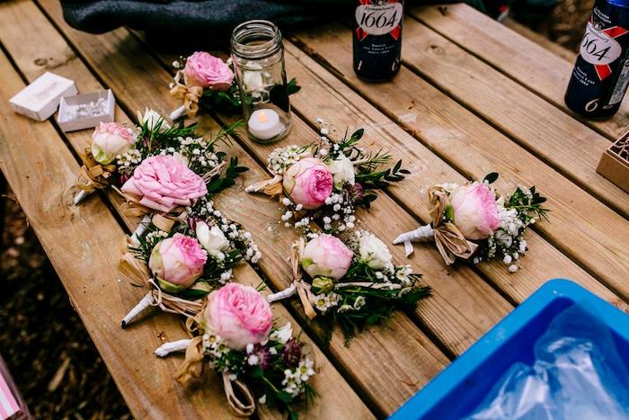 fleurs mariage champetre, exemple de boutonniere elegantes, sur une table en bois, bougeoir en bocal en verre