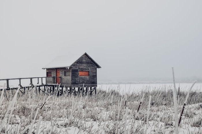 paysage hiver fond ecran, une plaine enneigée, une cabane simple au bord d un lac sous l emprise de la neige