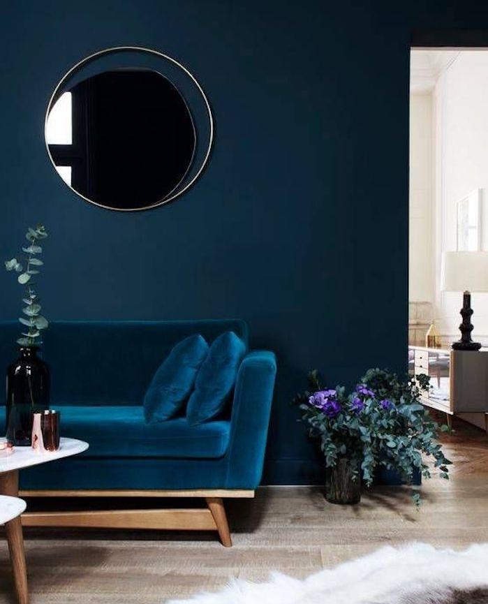 idée de canapé bleu pétrole adossé à un mur bleu marine avec un miroir rond accroché, parquet clair, table basse en bois, tapis peau animal