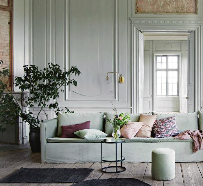 salon vert celadon en couleur peinture murale blanche et canapé vert gris, parquet marron, plante verte, coussins rose, bordeaux, vert et coloré, table noire minimaliste