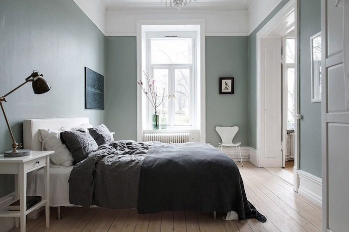 chambre aux murs couleur bleu celadon, deco scamdimabe, parquet clair, lit blanc avec linge de lit gris, table de nuit blanche