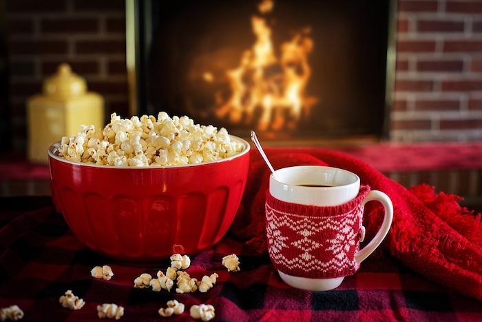 tasse de chocolat chaud, bol rempli de pop corn, couvertures rouges, cheminée romantique, ambiance cocooning, fond noel