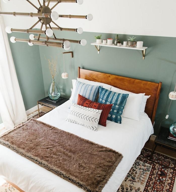 chambre design aux murs couleur vert de gris, en guise de tete de lit, lustre original, lit en bois avec linge de lit blanc, coussins en bleu, rouge et blanc, tapis oriental, étagère blanche rangement petites plantes
