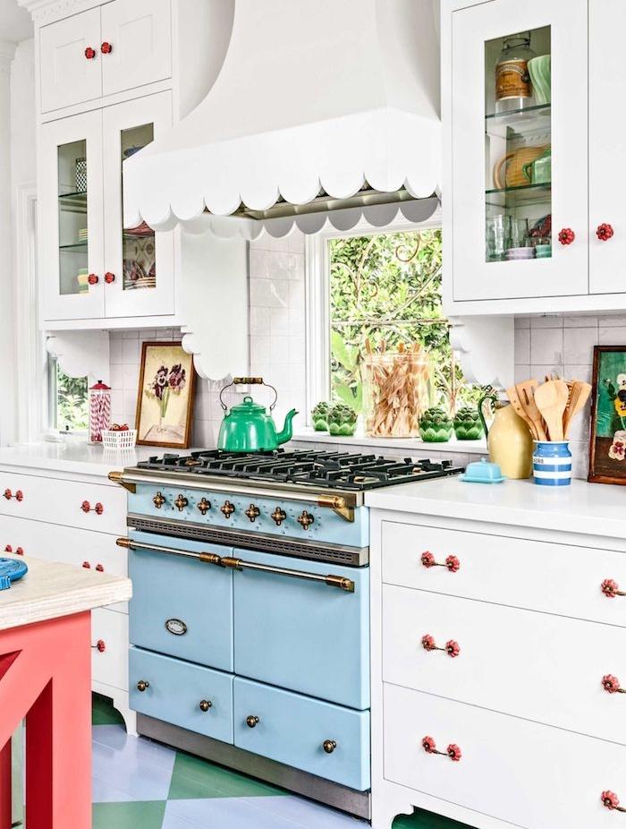 modele de cuisine campagnarde avec facade blanche et poignées de portes retro chic, piano de cuisson bleu pastel, carrelage bleu et vert et aspirateur blanc