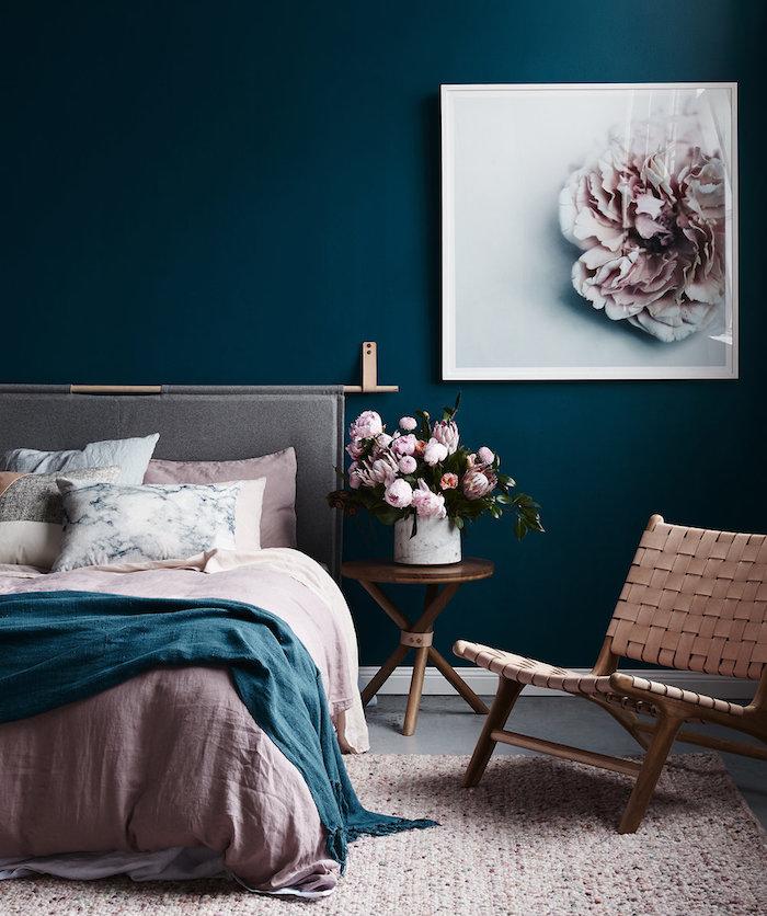 idée de deco chambre en rose et gris avec un mur de fond couleur bleu canard, nuance couleur pétrole, linge de lit et tapis rose, coussins effet marbre, bouquet de fleurs sur une table de nuit en bois