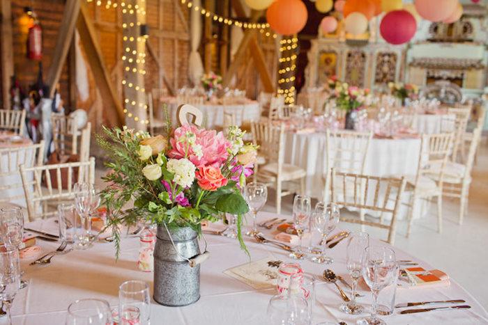 mariage champêtre, nappe blanche, pot à lait rempli de fleurs champetre, lanternes colorées et guirlande lumineuse