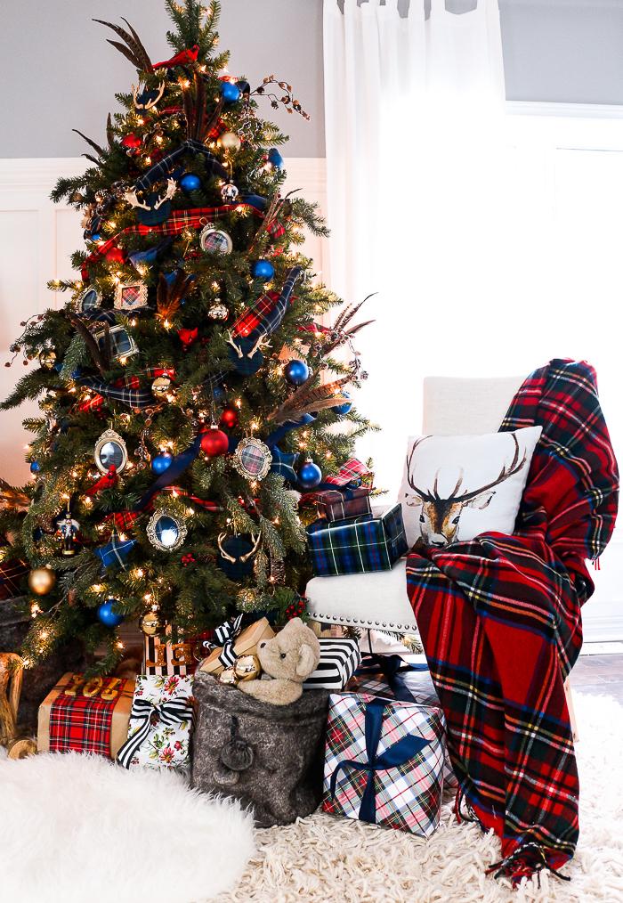 décoration sapin de noel en boules de noel rouges et bleues, guirlande en tissu rouge, deco de petits miroirs de poche vintage, pied de sapin en paquets cadeaux, chaise avec couverture et coussin à cerf