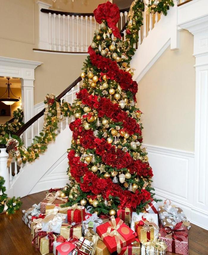 deco sapin de noel en ornements or et argent et guirlande de fleurs rouges, pied de paquets cadeaux, decoration escalier de guirlande