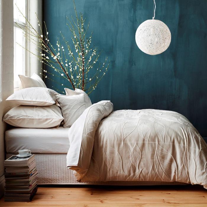 chambre à coucher couleur bleu pétrole en peinture murale couleur foncée, suspension boule blanche, linge de lit blanc, parquet clair, pile de magazines, arbre decoratifs