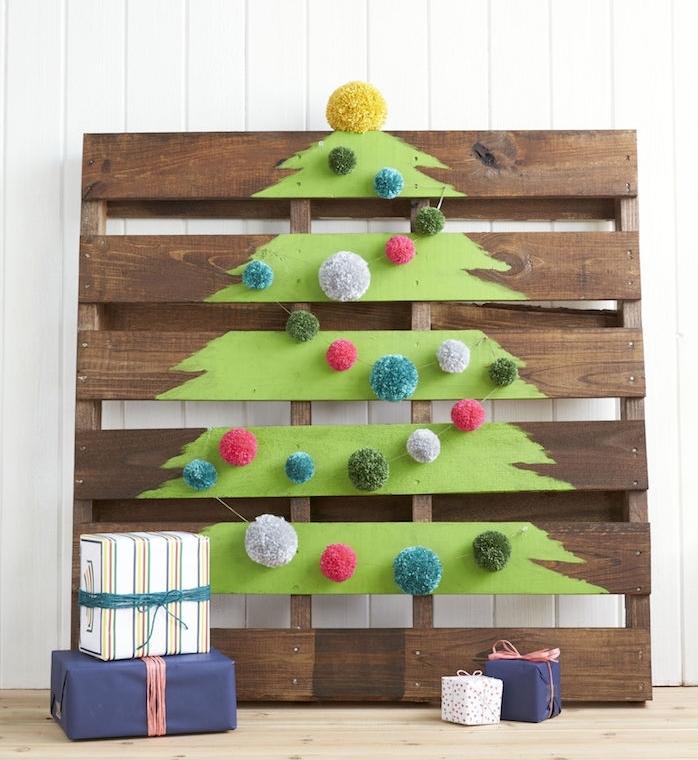 idée de sapin de noel en palette de bois, dessin sapin vert, décoré de guirlande de pompons colorés, cadeaux dans jolis emballages, activite noel