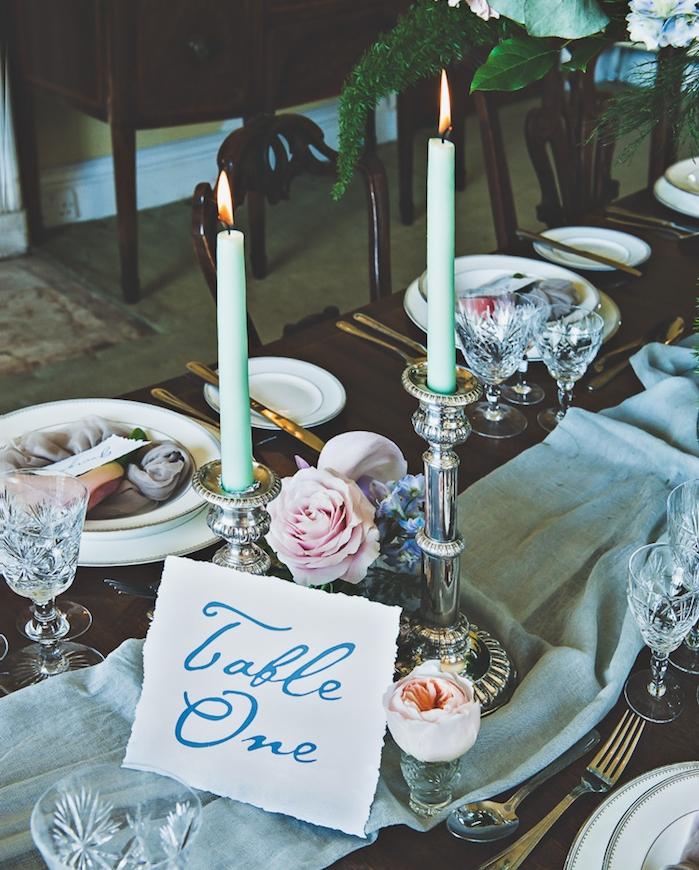 mariage champetre chic, chemin de table en tissu gris clair, soliflores, bougeoirs argentés, table en bois
