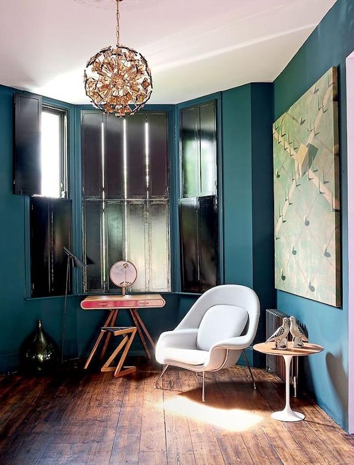 idée de deco salon bleu canard, teinte pétrole, parquet marron, chaise blanc cassé, suspension originale, fenêtres avec volets noirs et table design vintage
