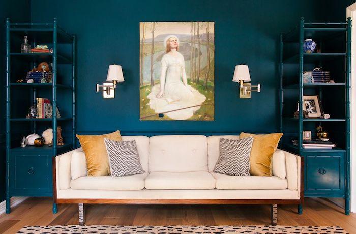 deco salon bleu petrole, mur de fond et étagères ouvertes couleur pétrole, canapé blanc cassé, coussins fauve et en noir et blanc, parquet marron, tableau peinture originale