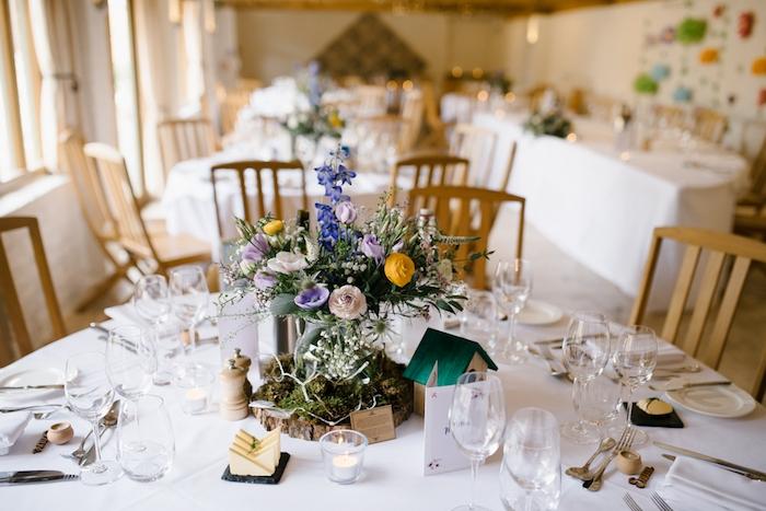 deco table mariage dans un style champetre, nappe blanche, rondin en bois couvert de mousse, vase de fleurs, petite maisonnette en bois