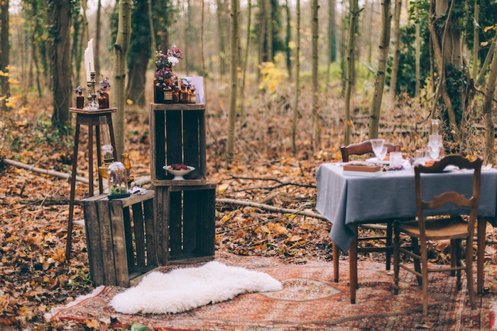 mariage champetre dans un cadre forestier, tapis oriental, table et chaises en bois, cagette bois, fioles et bouteilles fleuries