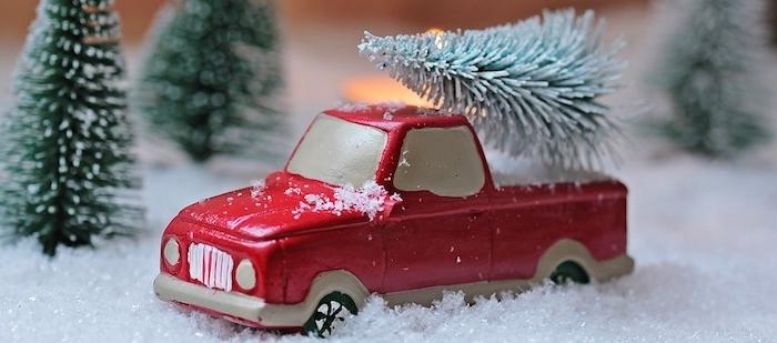 fond d ecran de noel en voiture miniature rouge sur une neige artificielle et sapins verts autour